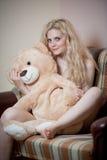 年轻白肤金发的肉欲的妇女坐放松与一个巨大的玩具熊的沙发 免版税图库摄影