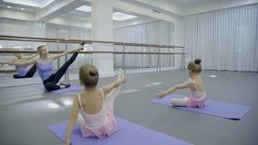 白肤金发的芭蕾老师带领stratching与她的明亮的健身房的两名小学生 影视素材