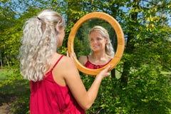 白肤金发的荷兰妇女看镜子本质上 库存照片