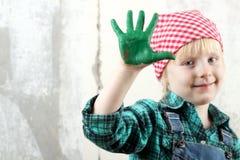 白肤金发的蓝眼睛的小女孩用在油漆的手 免版税图库摄影