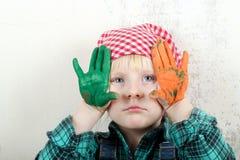 白肤金发的蓝眼睛的小女孩用在油漆的手 免版税库存照片