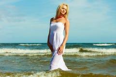 白肤金发的走在水中的妇女佩带的礼服 库存照片