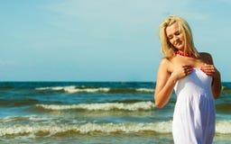 白肤金发的走在水中的妇女佩带的礼服 库存图片