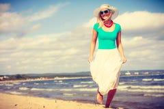 白肤金发的走在海滩的妇女佩带的礼服 库存照片