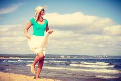 白肤金发的走在海滩的妇女佩带的礼服 库存图片