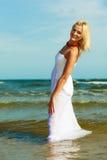 白肤金发的走在水中的妇女佩带的礼服 免版税库存图片