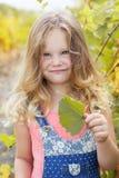白肤金发的逗人喜爱的儿童女孩在秋天葡萄园里 免版税库存照片
