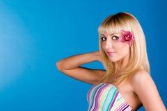 白肤金发的逗人喜爱的头发她的兰花 免版税库存图片