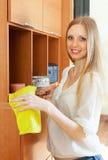 白肤金发的长发妇女清洁家具 免版税图库摄影
