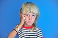 白肤金发的长的头发男孩画象谈话由手机 免版税图库摄影