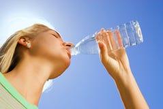 白肤金发的饮用的女孩水 免版税库存图片