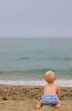 白肤金发的婴孩坐海滩 图库摄影