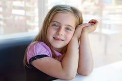 白肤金发的轻松的愉快的孩子女孩表示蓝眼睛 免版税库存照片