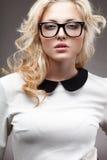 白肤金发的妇女佩带的镜片画象  免版税库存照片