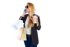 白肤金发的shopaholic妇女袋子和智能手机 库存图片