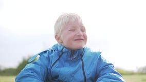白肤金发逗人喜爱的男孩坐草和哀伤 股票视频