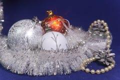 白色、红色和银色新年` s球在闪亮金属片在蓝色背景 免版税库存图片