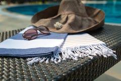 白色、蓝色和米黄土耳其厚绒毛巾、太阳镜和草帽在藤条懒人与蓝色游泳池作为背景 免版税库存图片
