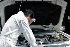 白色一致的感觉的沮丧的被注重的年轻技工人疲倦了与在开放敞篷的汽车在修理车库 库存照片