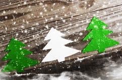 白色三棵由毛毡做的圣诞树和绿色在木,多雪的背景 工艺 库存照片