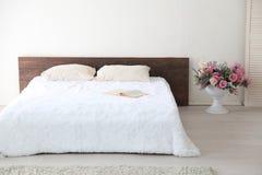 白色与床的卧室明亮的内部 免版税库存照片