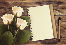 白色与笔记本和笔的玫瑰花 图库摄影