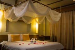 白色两只毛巾天鹅和红色玫瑰花瓣在床,蜜月装饰上 免版税库存照片