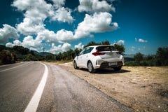 白色丰田Auris逗留在克利特海岛路的云彩中停放了  库存照片