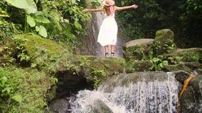 白色举胳膊和吸入新鲜的密林空气的礼服和草帽的少女在令人惊讶的瀑布 无忧无虑的生活方式旅行 股票视频
