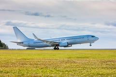 白色乘客空气喷气机在跑道离开 免版税库存照片