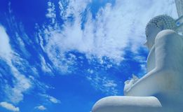 白色云彩和大白色菩萨雕塑在蓝天下 图库摄影