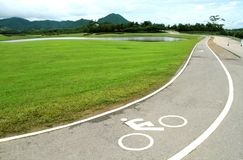 白色交通标志,在曲线柏油路的自行车道标志 免版税库存图片