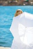 白色伞摆在掩藏的婚礼礼服的美丽的新娘 免版税图库摄影