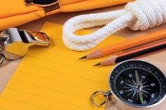 整洁白色侦察员绳索、围巾、口哨、指南针、铅笔和纸笔记 免版税库存照片