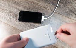白色便携式的力量银行和手机 图库摄影