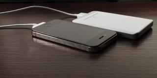 白色便携式的力量银行和手机 库存图片