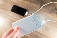白色便携式的力量银行和手机 免版税库存图片