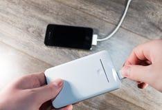 白色便携式的力量银行和手机 免版税库存照片