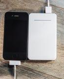 白色便携式的力量银行和手机 免版税图库摄影
