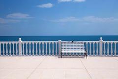白色俯视海的长凳、楼梯栏杆和空的大阳台 图库摄影