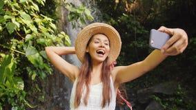 白色做Selfie照片的礼服和草帽的年轻愉快的混合的族种旅游女孩使用有惊人的狂放的密林的手机 股票录像