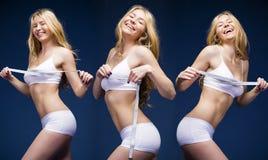 白色健身衣物的年轻美丽的白肤金发的妇女 免版税库存照片