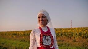 白色全国礼服的惊人的美女在向日葵的一个美好的领域站立 在日落的美丽的射击 影视素材