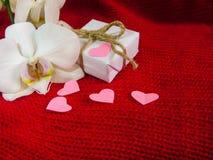 白色兰花和礼物盒在红色背景,情人节背景 小纸心脏 免版税库存图片