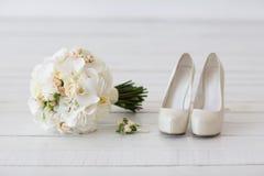 白色兰花和鞋子婚礼花束  免版税库存图片