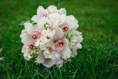 白色兰花开花在绿草的婚礼花束 免版税库存照片