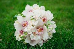 白色兰花开花在绿草的婚礼花束 库存图片