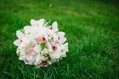 白色兰花开花在绿草的婚礼花束 图库摄影