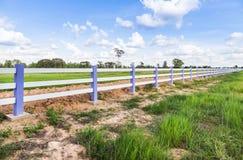 白色具体篱芭在绿色农场 免版税库存照片