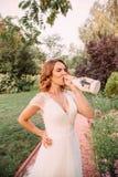 白色典雅的婚姻的长的礼服饮用的香槟的好和快乐,愉快的年轻白肤金发的女孩从a美妙地 免版税库存照片